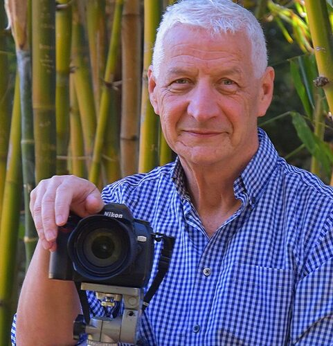 white haired man holding digital camera