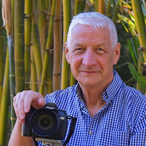 white haired man holding digital camera