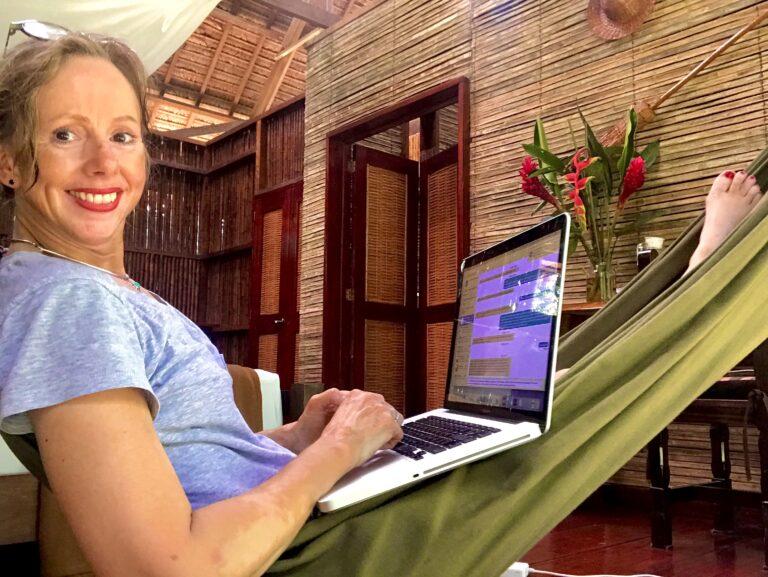 women in hammock on laptop