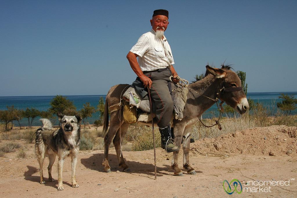 Man on donkey with dog behind
