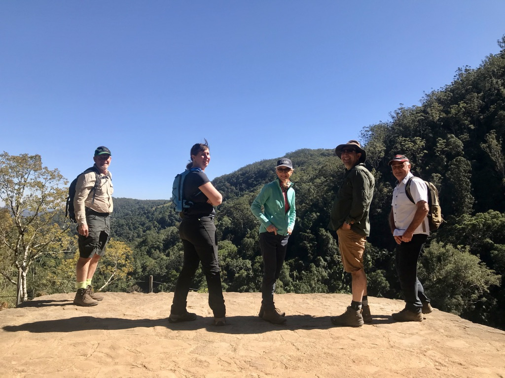 5 adults hikers stopped to enjoy the view of the hills around them