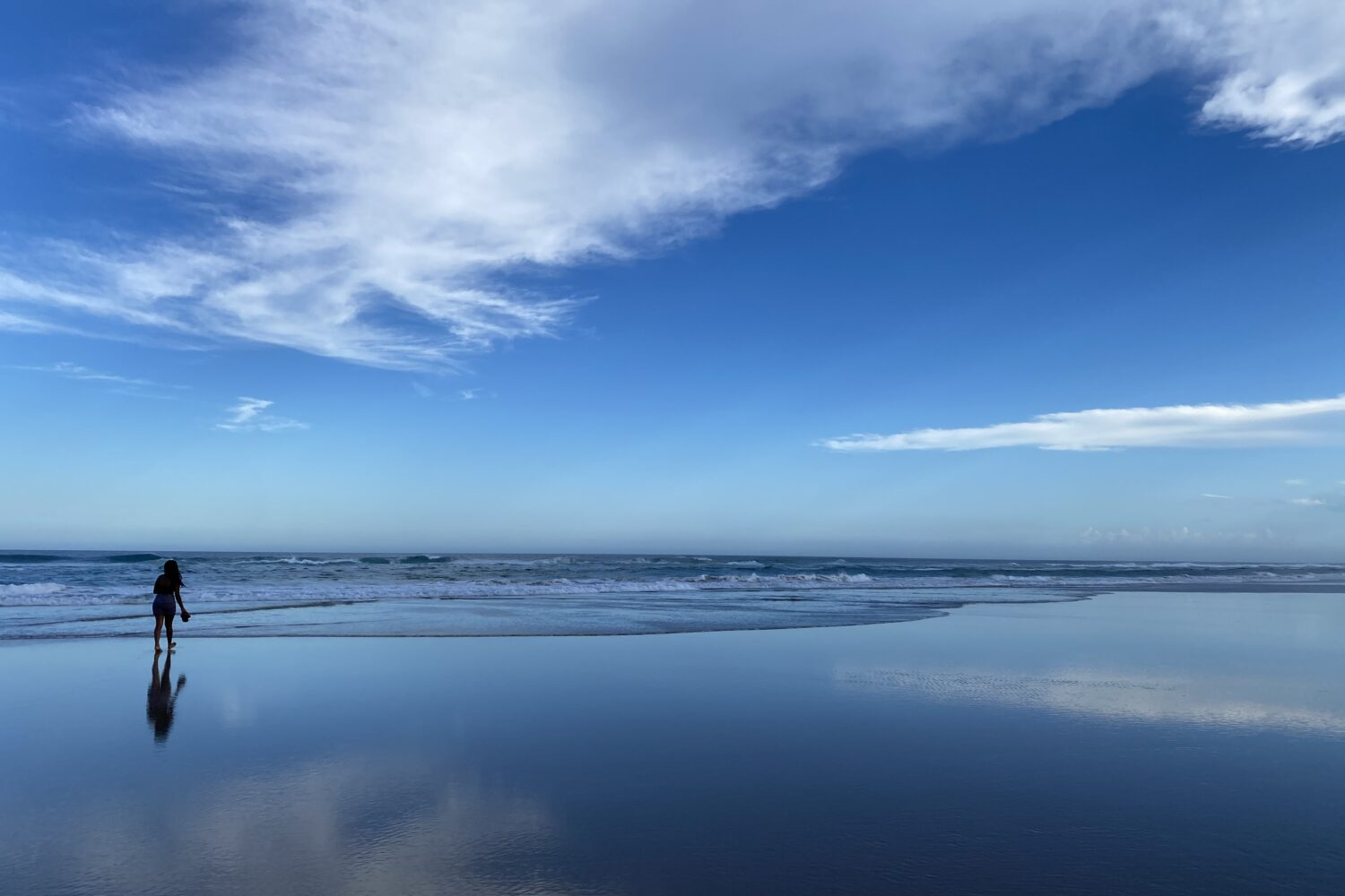 single person on beach with blue sky